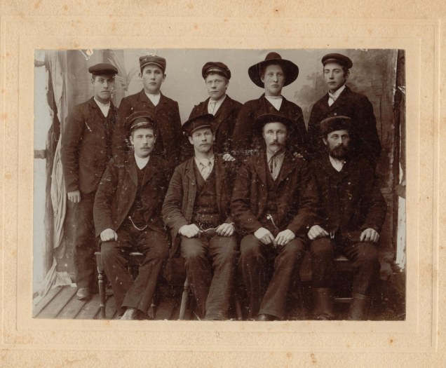 Picture of nine men, five standing, with four seated in front.
