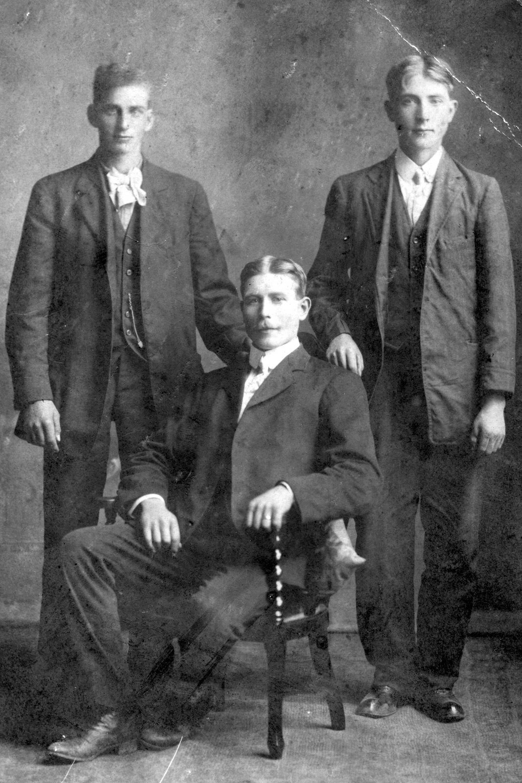 Picture of three men, two standing and one seated in the middle.